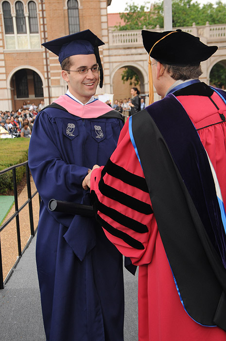 A graduation photo of someone receiving their diploma from the head of Rice University in Houston