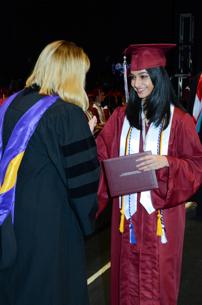A smiling student receives her diploma on the graduation day.